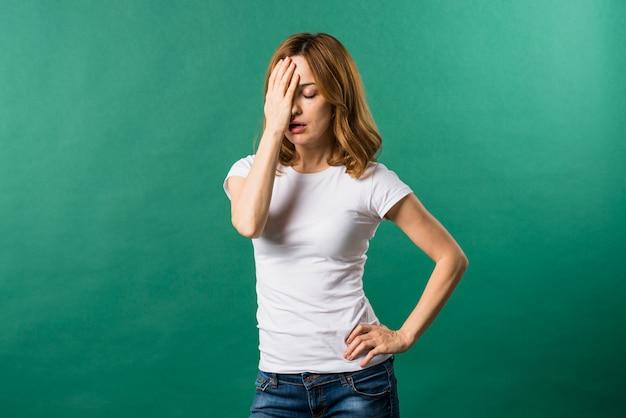 Portret van een bezorgd jonge vrouw tegen een groene achtergrond Gratis Foto