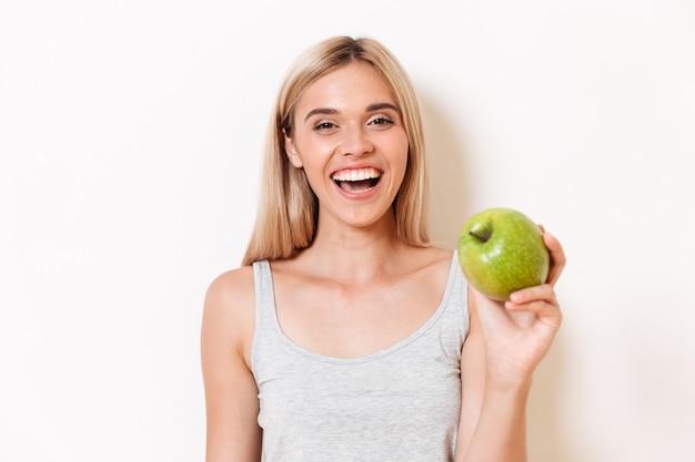 Portret van een blij meisje in ondergoed met groene appel Gratis Foto