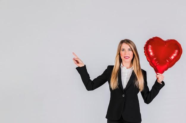 Portret van een blonde jonge onderneemster die rode folieballon houdt die ter beschikking haar vinger richt Gratis Foto