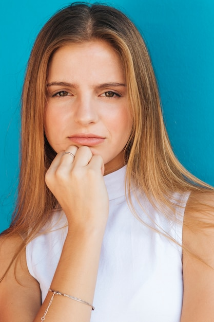 Portret van een blonde jonge vrouw die camera tegen blauwe achtergrond bekijkt Gratis Foto
