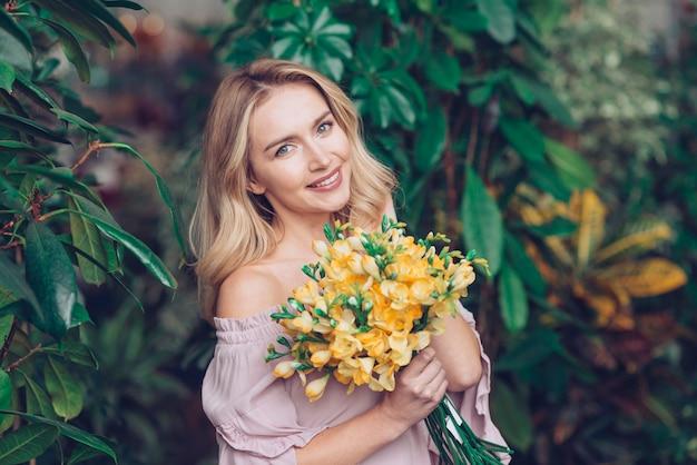 Portret van een blonde jonge vrouw die geel bloemboeket houdt Gratis Foto