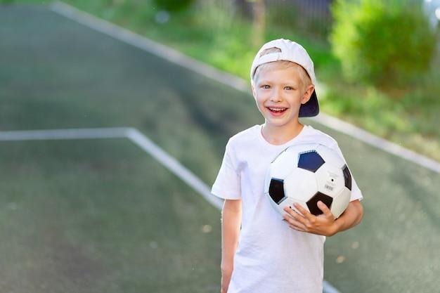 Portret van een blonde jongen in een pet in een sportuniform met een voetbal in zijn handen op het voetbalveld Premium Foto