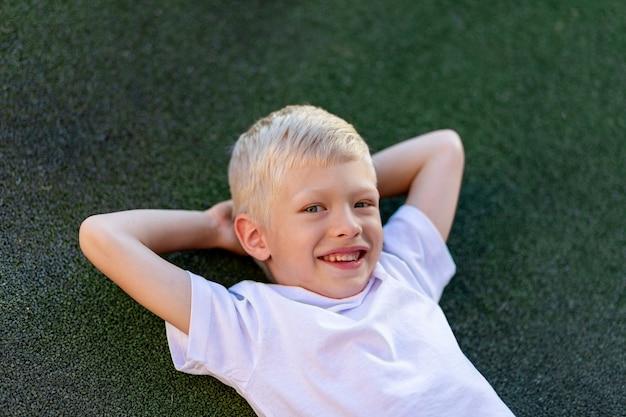Portret van een blonde jongen in een sportuniform liggend op het voetbalveld Premium Foto