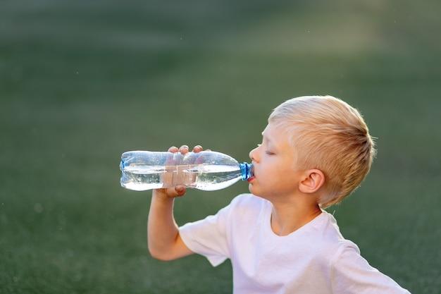 Portret van een blonde jongen in een sportuniform zittend op een groen gazon op een voetbalveld en drinkwater uit een fles Premium Foto