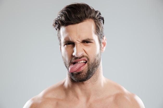 Portret van een boos geïrriteerde naakte bebaarde man met tong Gratis Foto
