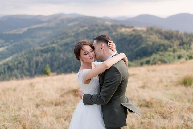 Portret van een bruidegom en een bruid alleen in de prachtige bergen op de zonnige zomerdag Gratis Foto