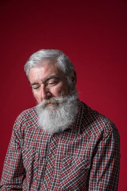 Portret van een depressieve senior man tegen rode achtergrond Gratis Foto