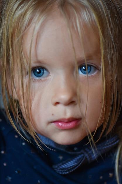 Portret van een droevig romantisch meisje met grote blauwe ogen van oost-europa, close-up, donkere achtergrond Premium Foto