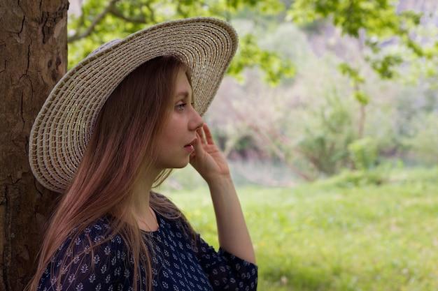 Portret van een dromerige vrouw in een hoed die zich in profiel dichtbij een boom bevindt en vooruit kijkt. Premium Foto