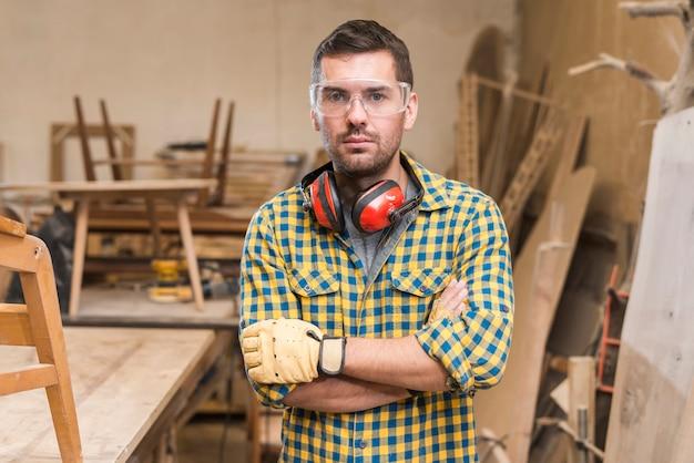 Portret van een ernstige mannelijke timmerman die zich in de workshop bevindt Gratis Foto