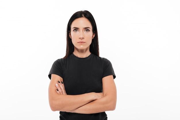 Portret van een ernstige vrouw die zich met gevouwen wapens bevindt Gratis Foto