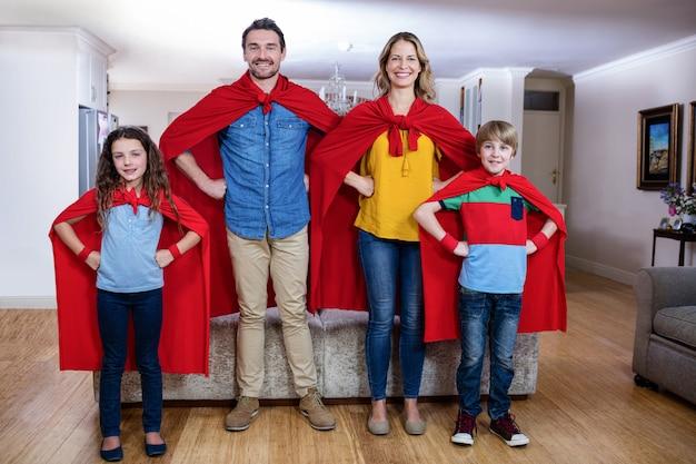 Portret van een familie die superheld in woonkamer beweert te zijn Premium Foto