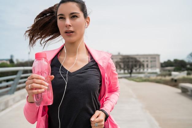 Portret van een fitness-vrouw die buiten in de straat loopt. sport en een gezonde levensstijl concept. Gratis Foto