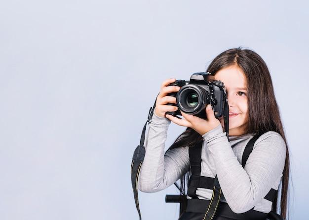 Portret van een fotograaf die haar gezicht behandelt met de camera tegen witte achtergrond Gratis Foto