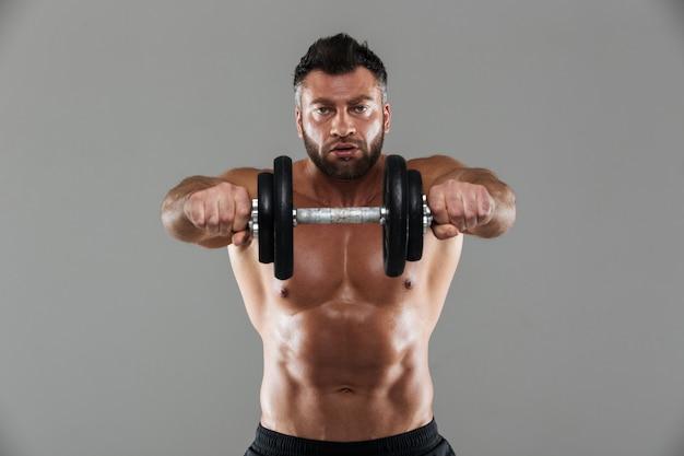 Portret van een geconcentreerde sterke shirtless mannelijke bodybuilder Gratis Foto