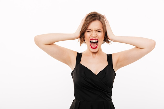 Portret van een gefrustreerd meisje, gekleed in zwarte jurk schreeuwen Gratis Foto