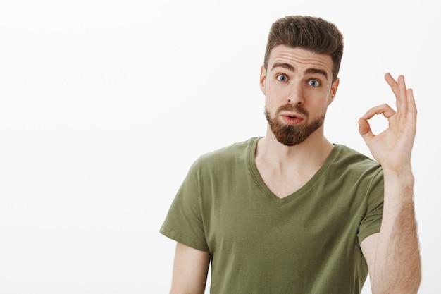 Portret van een geïmponeerde man die een geweldig idee bekijkt van een vriend die wauw en niet slecht zegt en oké gebaar laat zien dat wenkbrauwen optrekt als verbaasd over een mooi plan dat zich verbaasd stelt over een witte muur Gratis Foto