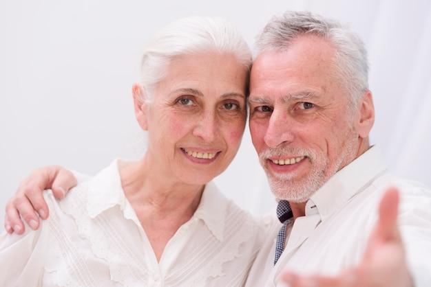 Portret van een gelukkig houdend van hoger paar die camera bekijken Gratis Foto