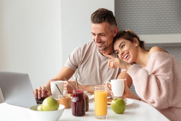 Portret van een gelukkig houdend van paar dat ontbijt heeft Gratis Foto
