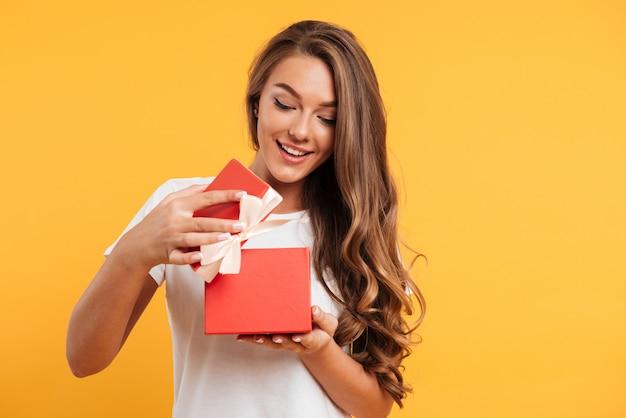 Portret van een gelukkig lachend meisje opening geschenkdoos Gratis Foto