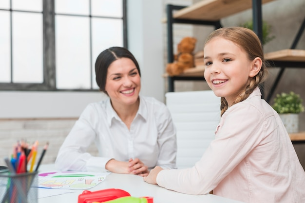 Portret van een gelukkig meisje met haar jonge vrouwelijke psycholoog in office Gratis Foto