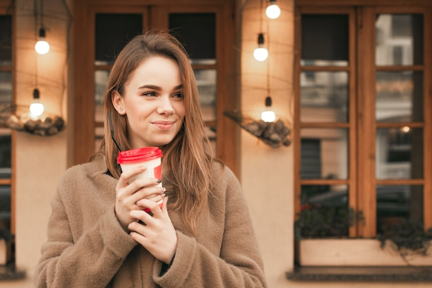 Portret van een gelukkig meisje staat op de achtergrond van een bruine muur met een kopje koffie in zijn handen, draagt lentekleren, kijkt zijwaarts en glimlacht Premium Foto