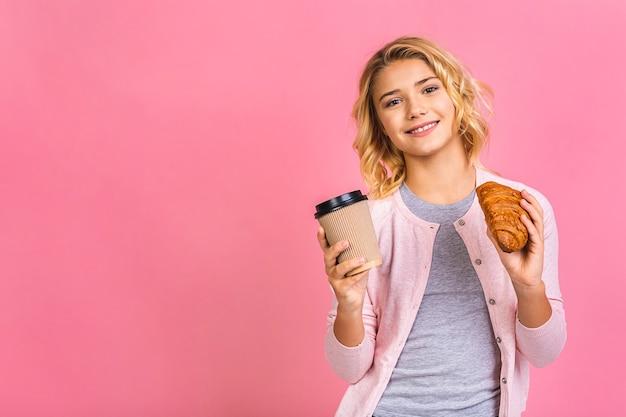 Portret van een gelukkig mooi meisje dat van het tienerkind croissant eet en een koffie drinkt Premium Foto