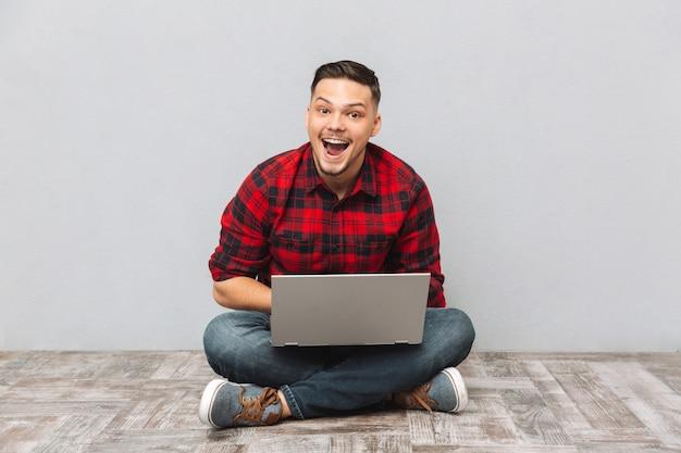 Portret van een gelukkig opgewonden man in geruite overhemd werken Gratis Foto