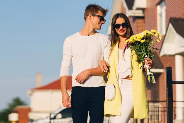 Portret van een gelukkig romantisch paar die in openlucht in europese stad bij de avond omhelzen. jonge mooie vrouw met bloemen. verliefde paar dating. Gratis Foto