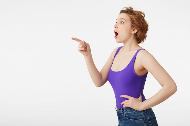 Portret van een gelukkig verbaasd jong aantrekkelijk korthaar meisje, gekleed in een paarse trui, zag iets ongelooflijk interessants en wijst met de vinger, kijk naar geïsoleerde kopie ruimte. Gratis Foto