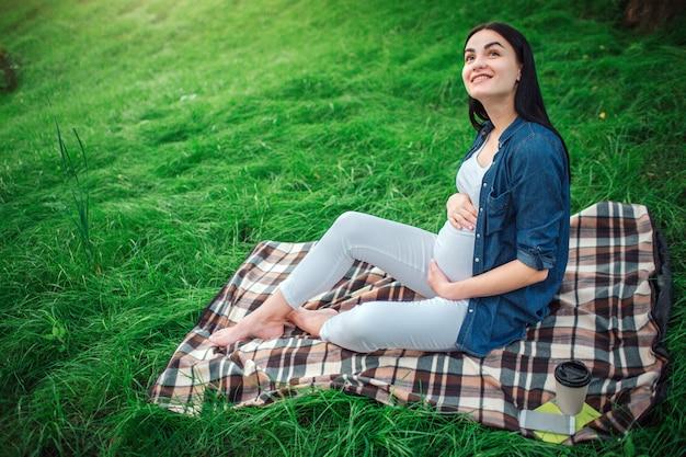 Portret van een gelukkig zwart haar en een trotse zwangere vrouw in een stad in het park. foto van vrouwelijk model wat betreft haar buik met handen. het vrouwelijke model zit op gras. Premium Foto