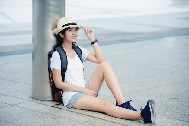 Portret van een gelukkige aziatische jonge vrouw zittend op de stad Gratis Foto