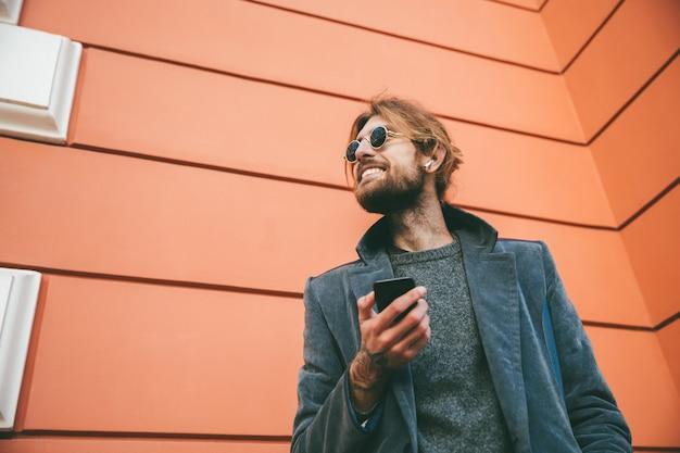 Portret van een gelukkige bebaarde man gekleed in jas Gratis Foto