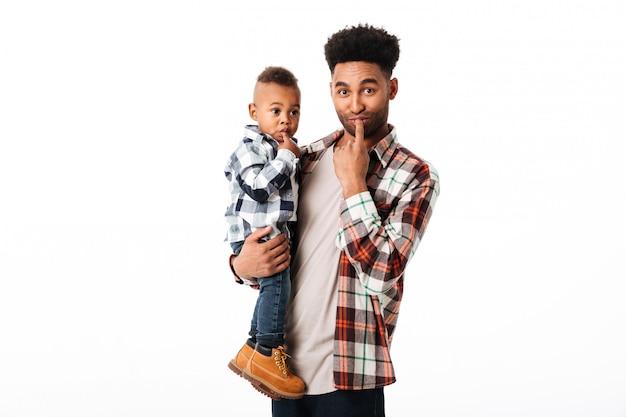 Portret van een gelukkige jonge afrikaanse man die zijn zoontje houdt Gratis Foto