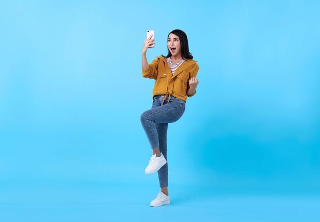 Portret van een gelukkige jonge aziatische vrouw die met mobiele telefoon viert die over blauwe achtergrond wordt geïsoleerd. Gratis Foto