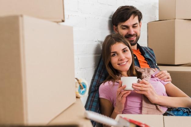 Portret van een gelukkige jonge paar zitten tussen de bewegende kartonnen dozen in hun nieuwe huis Gratis Foto