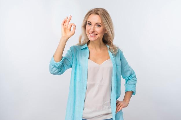 Portret van een gelukkige jonge vrouw die ok teken toont tegen witte achtergrond Gratis Foto