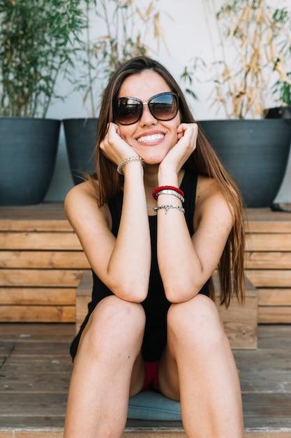 Portret van een gelukkige jonge vrouw die zonnebril draagt Gratis Foto