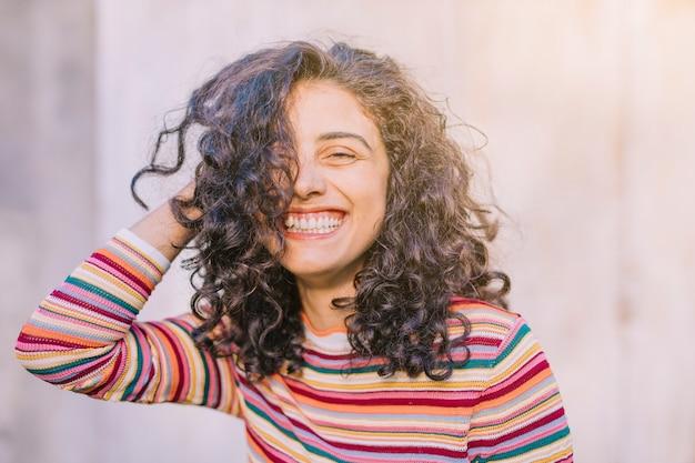 Portret van een gelukkige jonge vrouw met krullend haar Gratis Foto