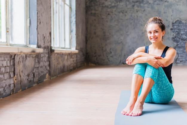 Portret van een gelukkige jonge vrouw zittend op oefening mat Gratis Foto