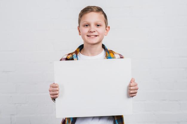 Portret van een gelukkige jongen die zich tegen witte muur bevindt die wit leeg aanplakbiljet toont Gratis Foto