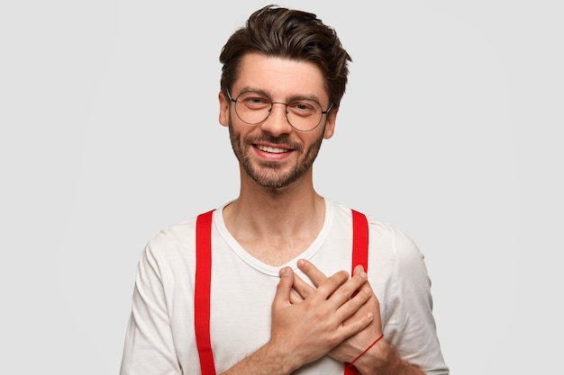 Portret van een gelukkige man houdt beide handpalmen op het hart, waardeert iets met grote dankbaarheid, gekleed in een stijlvolle outfit, heeft een vriendelijke glimlach, geïsoleerd op een witte muur. mensen, emoties, positiviteit Gratis Foto