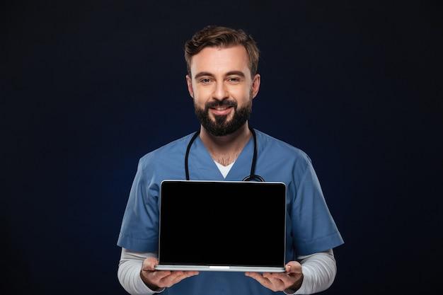 Portret van een gelukkige mannelijke arts gekleed in eenvormig Gratis Foto