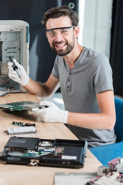 Portret van een gelukkige mannelijke technicus die aan computermotherboard werkt Gratis Foto