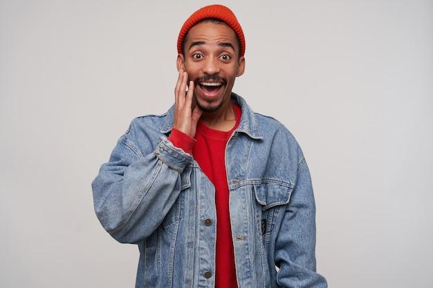 Portret van een gelukkige mooie jonge donkerharige bebaarde man met een donkere huid die gelukkig kijkt met een verbaasd gezicht en de palm op zijn wang houdt, geïsoleerd op wit Gratis Foto