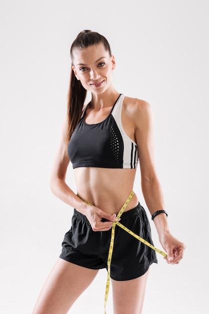 Portret van een gelukkige sportvrouw die haar taille meet Gratis Foto