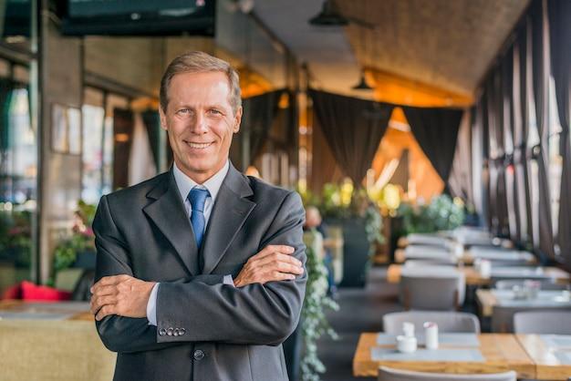 Portret van een gelukkige succesvolle zakenman die zich in restaurant met gekruist wapen bevindt Gratis Foto