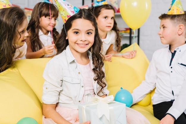 Portret van een gelukkige verjaardag meisje bedrijf presenteert in de hand zittend op de bank met haar vrienden Gratis Foto