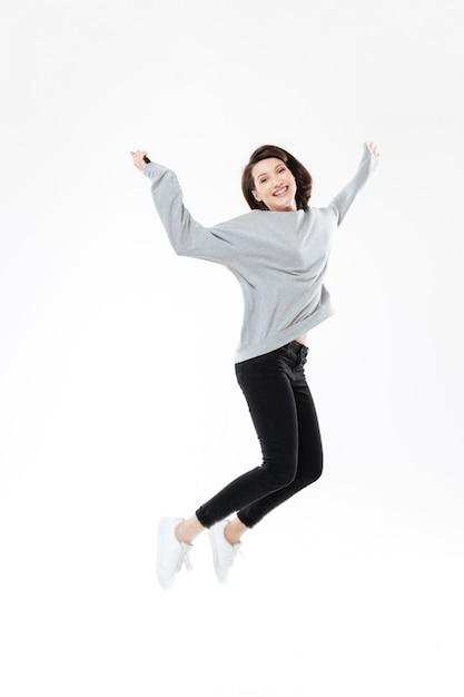 Portret van een gelukkige vrolijke vrouw die en succes springt viert Gratis Foto