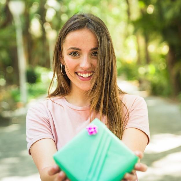 Portret van een gelukkige vrouw die met valentijnskaartgift camera bekijkt Gratis Foto